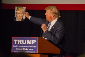 Donald Trump holds up magazine cover featuring himself.